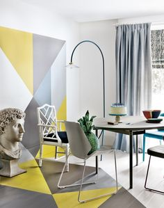 Opt for a bold pain technique over wallpaper like this striking geometric grey and yellow dining room