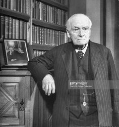 Dr. John Neville Keynes posing in front of bookcase in his studio.