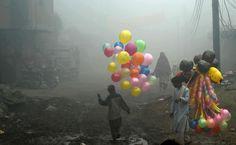 Pakistani balloon vendors cross a street in heavy fog in Lahore.