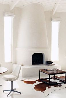 The fireplace, an awkward eyesore, became a nod to the Greek isles with the same white-plaster treatment used on the walls of the main house.