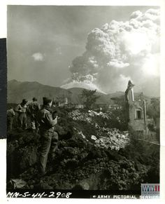 """Volcanic damager in San Sebastiano, Italy on 24 March 1944 """"MM-5-44-2908""""; Sig.[Signal] C[Corps] photo-3-24-44. Italy. Mt. Vesuvius belches huge clouds of smoke and volcanic ash over the remains of San Sebastiano, Italy, partially destroyed by the lava stream from the erupting volcano."""" San Sebastiano, Italy. 24 March 1944."""