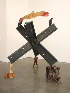 "Matthew Day Jackson, ""Tomb of the Unknown,"" 2005, carved, scorched and wood-burned scrap wood, broken  skateboard, Sculpey, coloured pencil, wood l-beam supports"