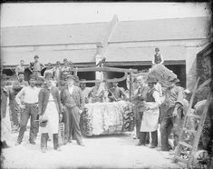 A group of men is gathered around a cotton bale that is being weighed. They all look directly at the camera, and several of the men hold tools in their hands. Three men wear white aprons, and almost all have hats. Loyola University New Orleans, Louisiana State University, Louisiana History, Louisiana Tech, Oral History, Teaching History, Coding Languages, Types Of Resources, White Apron