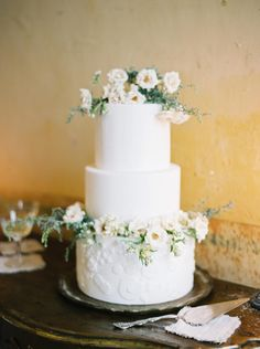 White wedding cake with textured bottom layer and sugar flowers