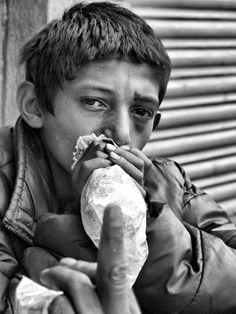 Boy huffing shoe glue (Rugby) on the streets of Kathmandu Nepal
