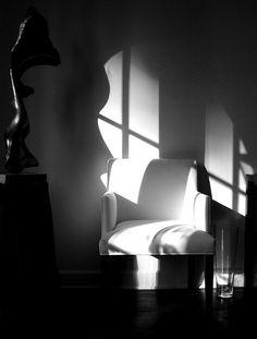 Window pane shadow, white chair, white wall, statue