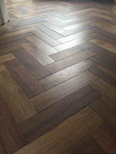 Dark wood effect porcelain floor tiles laid in a herringbone pattern