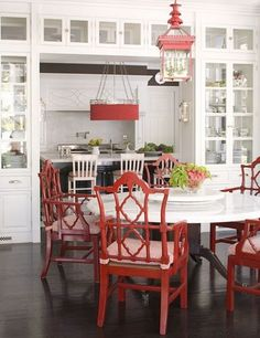 I especially like the eating nook that's tucked in under the glass-front cabinets & between the kitchen & dining area - also the white & red contrast & red lantern lighting