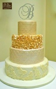 Vintage Lace & Ruffle Wedding Cake. Ivory & Champagne colored wedding cake with sugar ruffles, lace appliques and quilting.
