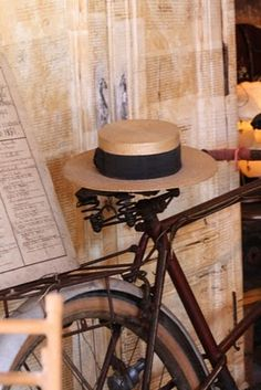 A bicycle and boater hat resting while it's owner has a leisurely lunch.