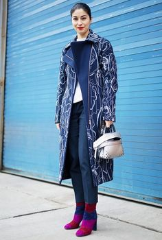A printed coat adds interest to a white tee, blue trousers and metallic bag worn with colorblocked booties