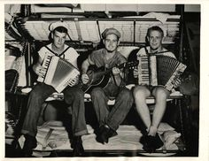 1944- U.S. Coast Guardsmen, back on their transport after participating in the beachhead victory at Aitape, pull out their accordions and guitar for musical celebration.