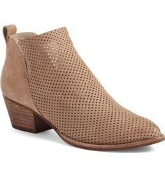 Breezy, laser-perforated leather adds depth and texture to this Western-inspired pointy-toe bootie set on a chunky setback heel.