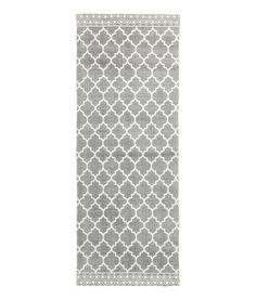 Grau. Langer Webteppich aus Baumwolle mit Musterdruck auf der Oberseite.