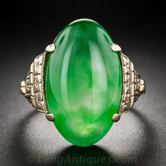 Vintage Natural Jade Ring. This highly translucent and sizable (3/4 by 1/2 inch) double cabochon displays a lush glowing green color with an enchanting play of variegated hues that the most expert photography cannot begin to capture. The gorgeous gemstone is tastefully presented in a 14K rose gold mounting adorned with classic hand engraved Art Deco floral and foliate design elements.