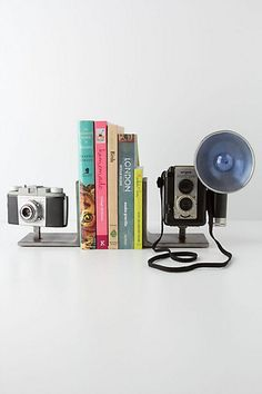 Instead of C's old cameras just sitting on the shelves, they can DO something. I could probably make these with a regular tripod adapter & some bookends.