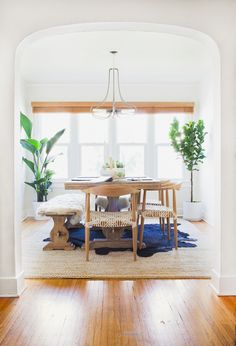 Dining space with wall of windows | Neutral colors, natural light and large plants
