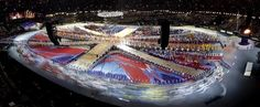 Athletes enter the Olympic Stadium during the Closing Ceremony at the 2012 Summer Olympics, Sunday, Aug. 12, 2012, in London. (AP Photo/David J. Phillip)  A giant model of a portrait of John Lennon is made with panels carried by performers during the closing ceremony of the London 2012 Olympic Games