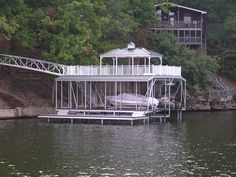 Wahoo floating aluminum double slip boat dock with step-down swim platform. Combination sun and shade upper deck with corrugated metal hip roof and cupola and front-to-back gables on the sides. Arched gangway with aluminum railing connects the dock to shore.