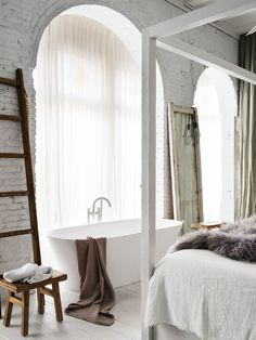 Glamorous master suite with canopy bed, arched floor-to-ceiling windows and a modern, freestanding bathtub.