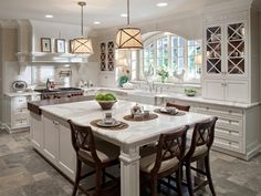 A large window above the farmhouse sink allows plenty of natural light to flow throughout this bright white traditional kitchen. Two large pendant drum lights hang over the island, clad in a pattern that mimics the mullion pattern of the glass-front cabinet doors.