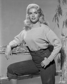 Jayne Mansfield Posed in White Tweed Long Sleeve Round Neck Shirt and High Waist Black Pants with Right Arm Rest on the Wood Fence Premium Art Print