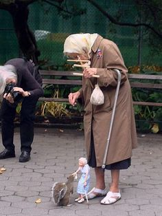 Doris Deither, 85, and her marionette, feeding a squirrel in New York. Photo by Nathalie Kalbach.