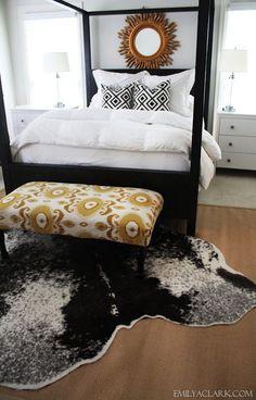 Layering rugs in our bedroom, cowhide over sisal rug