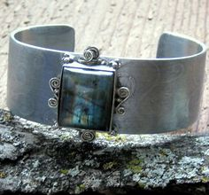 Labradorite Etched Aluminum Cuff Bracelet - Aluminum cuff bracelet is etched with a scroll pattern and accented with a recycled labradorite stone set in sterling silver. Each end is stamped with a tiny dragonfly. The cuff is 1 wide and 2 3/8 across, with a 1 1/8 opening. Can be adjusted by slightly bending. All materials have been recycled.  Please visit our shop for more unique jewelry and accessories: https://www.etsy.com/shop/EponasCrystals   Eponascrystals.etsy.com jewelry designs are…