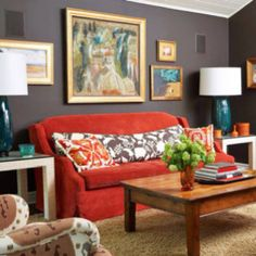 dark grey walls - lots of art, gold frames, red sofa - living room