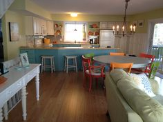 Beach house kitchen. Love the different colored chairs around the table!