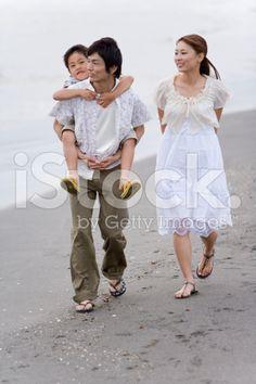 砂浜のビーチに沿って歩く家族 – ロイヤリティフリーのストックフォト
