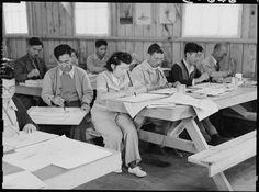 San Bruno, California. An art school has been established at this Assembly center with a well trained, experienced evacuee staff under the leadership of Professor Chiura Obata, who before evacuation was an associate professor of art at the University of California. This photograph shows part of the morning class learning free hand brush strokes on June 16, 1942. By Dorothea Lange, War Relocation Authority photographer.