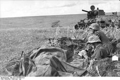 Two Grenadiers with Maschinengewehr (MG take an opportunity to eat their meager field rations next to a destroyed Soviet Panzer Photographer: PK. German Soldiers Ww2, German Army, Military Photos, Military History, Luftwaffe, Mg34, Ww2 Photos, Panzer, War Machine