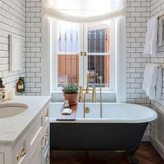 Floor-to-ceiling tiles emphasize the height of this bathroom, while the monochrome colour scheme gives it a sense of serenity. Via housetohome.co.uk