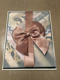 A brown and white birthday note with a stain bow on top of acetate covering strips of decorative paper.