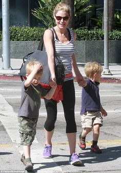 Doting mum: Julie was seen smiling as she held her sons' hands as they walked along