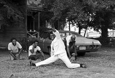 "James Brown does a split in Augusta, Georgia, 1979. ""When I arrived, James Brown had his hair in curlers. He told me to jump in his car and he would show me his town. He stopped the car from time to time, jumped out, ran into someone's yard, and did the split, singing 'I Feel Fine.' The people in the yard were astounded and started laughing."""