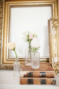 roses in vintage bottles with gold vintage frames #vintage #weddingdecor #weddingchicks http://www.weddingchicks.com/2014/02/06/simple-comforts-wedding-inspiration/