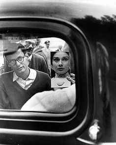 Audrey Hepburn looking herself in the mirror as Richard Avedon watches her, 1959.