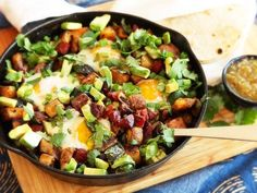 Ultra-crisp potatoes fried in chorizo fat with chunks of chorizo, seared green chilies, and scallions, all topped with baked eggs, avocado, and cilantro. It's a heck of a way to start the day.