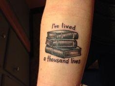 ein Stapel Bücher mit Spruch auf dem Unterarm