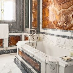 Juan Pablo Molyneux's Pebble Beach project in August Architectural Digest includes this bath, paneled in distressed oak, grey onyx, and red marble, with a Calacatta marble tub surround. (marble from Carmel Stone Imports; tub fittings by Waterworks).