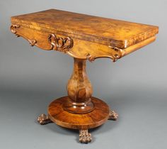 """Lot 1153, A Victorian figured walnut card table with carved apron and baluster turned column, raised on a circular base with paw feet 29""""h x 35 1/2""""w x 13 1/2""""d, est  £150-200"""