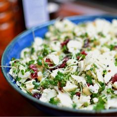 A salad with thinly sliced raw cauliflower, watercress, hazelnuts, dried cranberries, and a simple oil and cider vinegar dressing