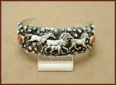 """Unique and beautiful! This handmade sterling silver bracelet is made and signed by Navajo artist Emer Thompson. The cuff has an oxidized silver finish with running horses, round silver drops and Spiny Oyster Shell gemstones on each side. The cuff measures 1.01"""" wide, has an inside measurement of 5.70"""" and an opening of 1.23"""""""