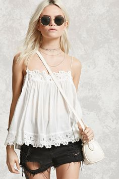 A textured woven top featuring cami straps, a billowy silhouette, and eyelet crochet trim along the neckline and vented hem.