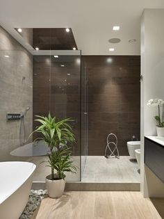 Master bathroom, wood grain tile floor and wall, glass shower, free standing tub on stones | Fedorova