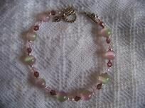 Pink and Green Rainbow of color is beautiful and accented with pink and purple Swarovski Crystals. It has a Dragonfly toggle clasp and is approx. 7 1/2   I make and create one of a kind jewelry from natural stone, shell,wood,bone,horn,teeth, feathe...