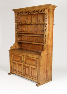 An Irish pine dresser with open plate rack and Celtic knot carving; with double bead crown molding, three plate rack shelves, a pair of raised panel doors with brass pulls and scalloped apron raised stepped feet; circa 1870; #dresser #sideboards #home #celtic #celticknot #diningroom #cabinet #Irish #kitchen #pine #sf #sanFrancisco #designinspiration #homedecor #interiordecorating #interiordesigner #countryliving #countrydecor
